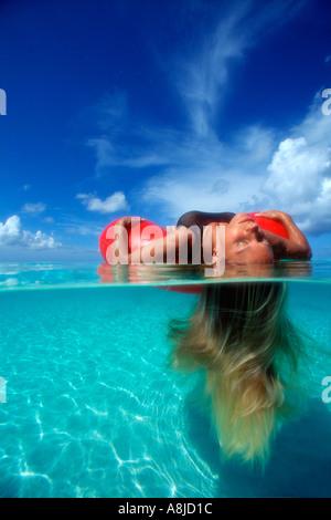 Grand Cayman Seven Mile Beach moins sur les femmes de flotte dans le tube intérieur rouge cheveu qui coule Banque D'Images