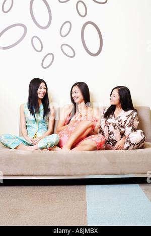 Trois jeunes femmes assises sur un canapé Banque D'Images