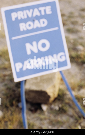 Signe de flou artistique sur les jambes grêles et appuyé par une pierre disant chemin privé Pas de parking Banque D'Images