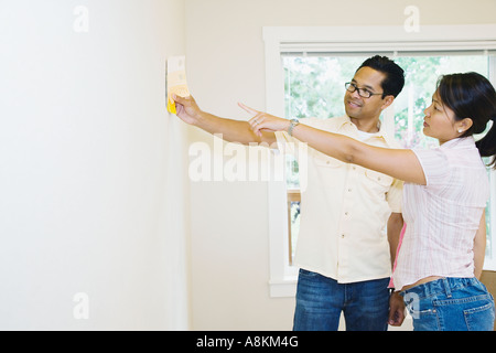 Asian couple looking at paint swatches in new house Banque D'Images