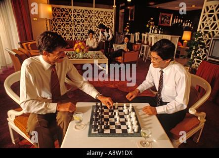 Deux hommes assis à l'intérieur jouant aux échecs dans le salon de l'hôtel.