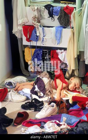 Enfant en chambre des parents penderie reposant après avoir fait un énorme gâchis de chaussures et vêtements Banque D'Images