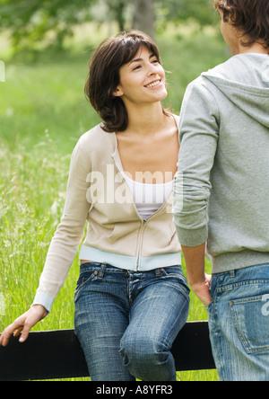 Jeune femme assise sur une clôture en bois à au jeune homme Banque D'Images