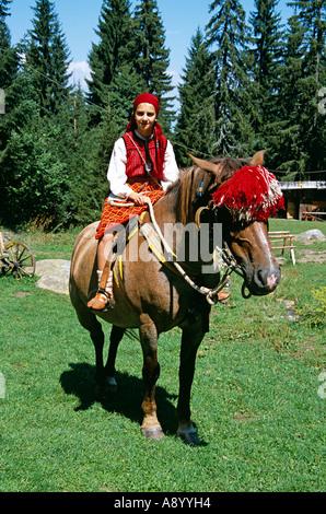 Fille habillé en costume national assis sur le cheval, Chalin Valog, Pirin, près de Bansko, Bulgarie Banque D'Images