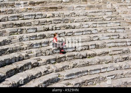 Femme assise seule sur sièges en pierre dans la 5e siècle BC Théâtre Grec Ségeste Sicile Italie Banque D'Images