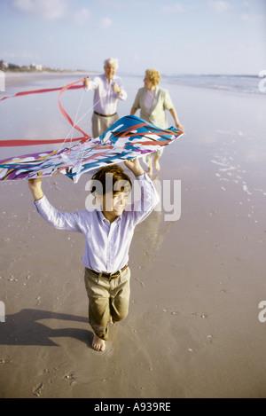 Vol de l'enfant d'un cerf-volant sur la plage avec ses grands-parents Banque D'Images