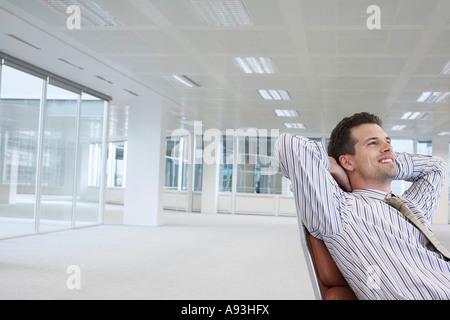 Employée de bureau en se penchant en arrière dans la chaise pivotante, les mains derrière la tête, dans l'espace Banque D'Images