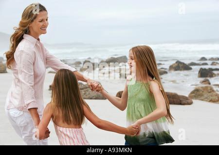 Mère jouant avec deux filles (7-9, 10-12) on beach Banque D'Images