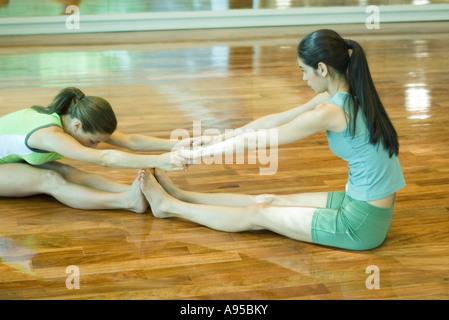 Deux jeunes femmes assises sur plancher du gymnase, pieds à pieds, stretching Banque D'Images