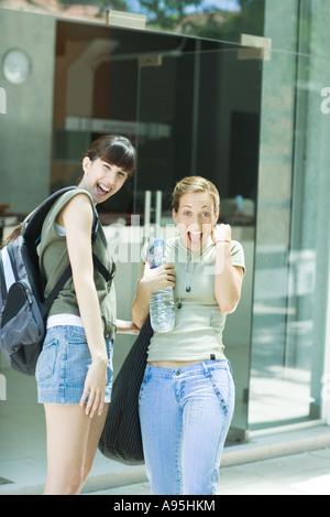 Deux jeunes femmes se tenant ensemble, l'un tenant une bouteille d'eau, rendant heureux visage et fist Banque D'Images