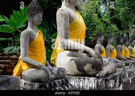 Bouddhas ou Rupa avec leur robe safran d'or situé au Wat Yai Chai dans Monghon la vieille ville Ayutthaya, Thaïlande. Banque D'Images