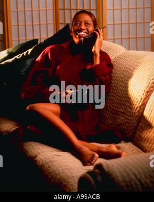 African American Woman dans un peignoir assis sur le canapé en parlant au téléphone avec une tasse de café Banque D'Images
