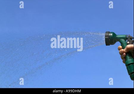 La pulvérisation de l'eau d'un sprinkleur arrosage contre un ciel bleu Banque D'Images