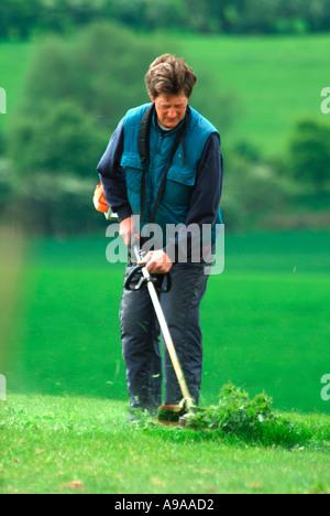 Un homme strimming mauvaises herbes dans un enclos à l'aide d'un strimmer à essence Banque D'Images
