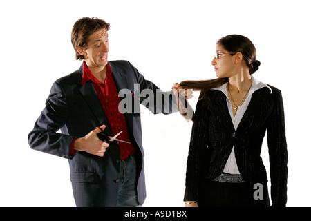 Jeune femme et homme en costume d'affaires jouer des ciseaux Banque D'Images