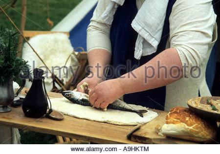 Dame en costume médiéval préparer un poisson pour la cuisson en friture Banque D'Images