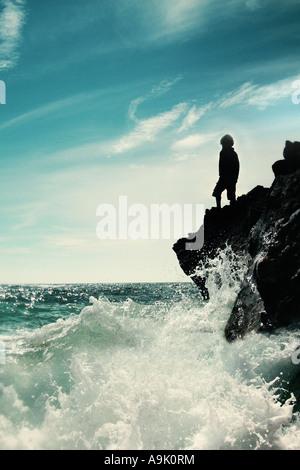 Jeune garçon se tenait sur le bord de roches avec le fracas des vagues Banque D'Images