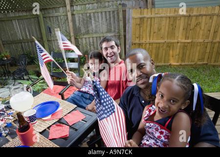 Deux jeunes filles avec les papas au 4 juillet barbecue en agitant des drapeaux américains Banque D'Images