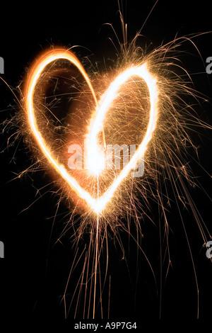 Forme de coeur pétillant de nuit avec les cierges magiques