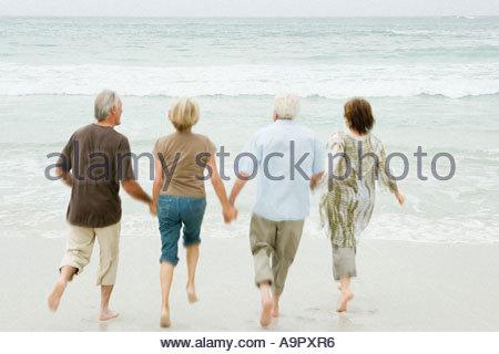 Quatre hauts adultes fonctionnant dans la mer Banque D'Images