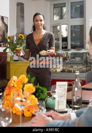 Serveuse apportant de la nourriture à la table Banque D'Images