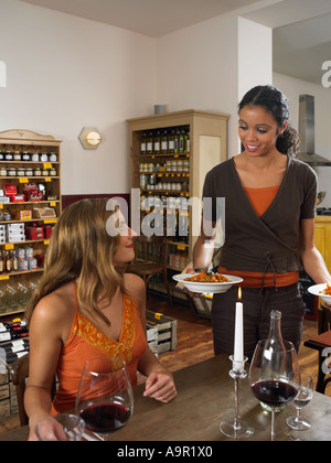 Serveuse apportent de la nourriture à couple in restaurant Banque D'Images