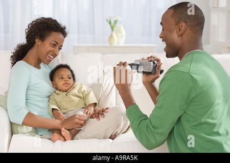 L'enregistrement vidéo Père Mère et bébé sur canapé Banque D'Images