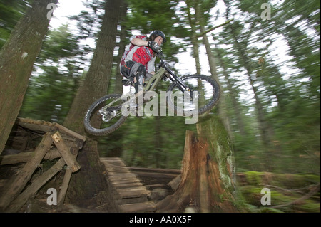 Vélo de montagne équitation Jumping off un sentier du Bois de la Côte-Nord Vancouver Canada Banque D'Images