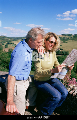 Couple in field looking at map Banque D'Images