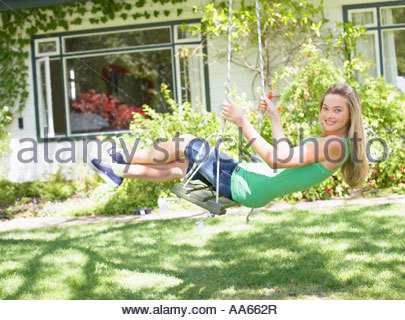 Teenage girl on swing outdoors in yard Banque D'Images