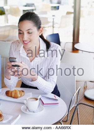 Femme dans un café de sms sur son téléphone portable Banque D'Images