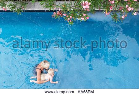 Mère avec bébé dans la piscine avec des fleurs Banque D'Images