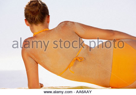 Rear view of woman in bikini with sand on retour Banque D'Images