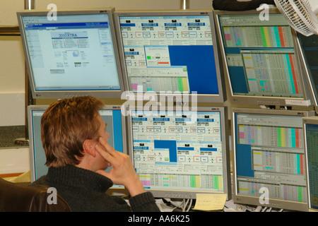 Un concessionnaire de sexe masculin dans les marchés financiers de la City de Londres est assis à son bureau à la Banque D'Images