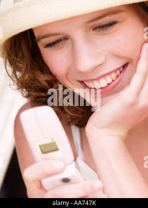 Teenage girl young woman reading message texte SMS à partir de son petit ami sur son téléphone portable l'amour Banque D'Images