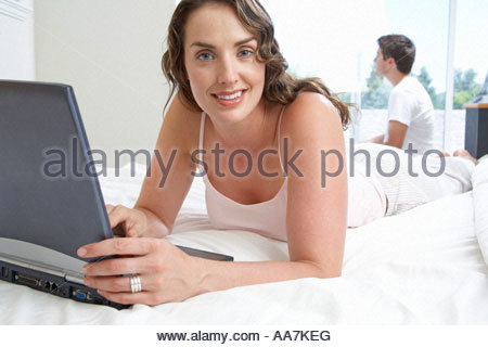 Young woman using laptop in bed Banque D'Images