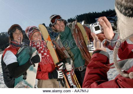 Friends smiling caméra sur une piste de ski Banque D'Images