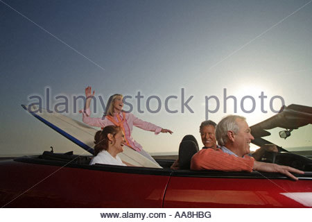 Les couples d'âge mûr riding in convertible with surfboard Banque D'Images
