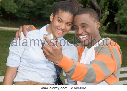 Teenage couple taking own photograph outdoors Banque D'Images