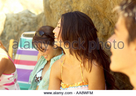 Teenage girl leaning on rock on beach Banque D'Images