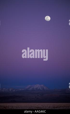Moonrise Salar de Atacama désert d'Atacama au Chili des tons de rose et violet remplir l'air illuminent les sommets Banque D'Images