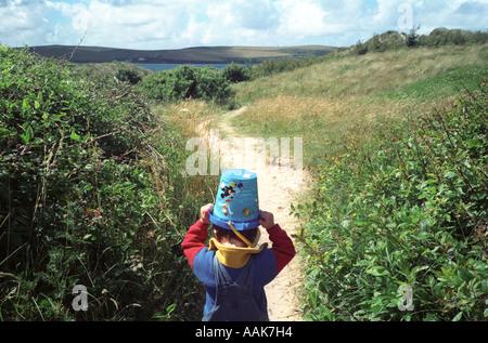 Un jeune garçon transporte un seau sur la tête en marchant le long d'un chemin côtier, Rock, Cornwall, UK. Banque D'Images
