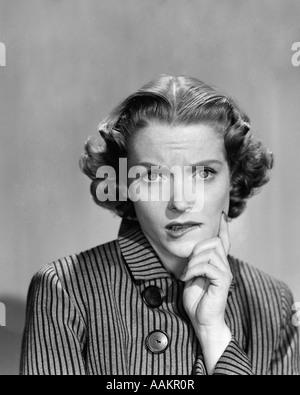 Années 1950 Années 1960 femme en robe rayée AVEC DES BOUTONS À CÔTÉ DE LA BANDE DESSINÉE D'EXPRESSION INQUIÈTE CHIN Banque D'Images