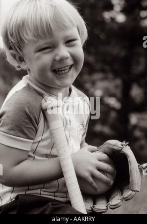 1980 jeunes rire garçon blond avec un gant de baseball & BAT SMILING AT CAMERA Banque D'Images