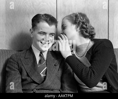 Années 1930 Années 1940 YOUNG TEENAGE COUPLE SITTING ON COUCH GIRL WHISPERING EN SECRET SMILING BOY'S EAR Banque D'Images