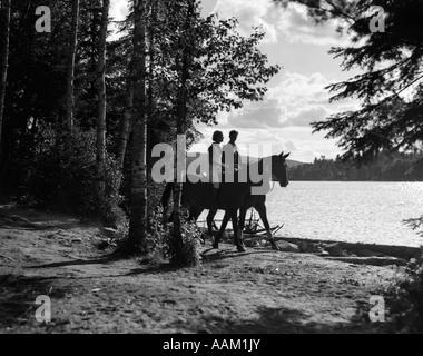 1930 MAN & WOMAN RIDING HORSES PAR ZONE BOISÉE LE LONG DU LAC Banque D'Images