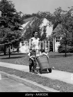 1950 MAMAN SUR TROTTOIR poussant l'OSIER PANIER AVEC LA FILLE ET LE FILS DANS LA MARCHE À côté de son chapeau de Banque D'Images