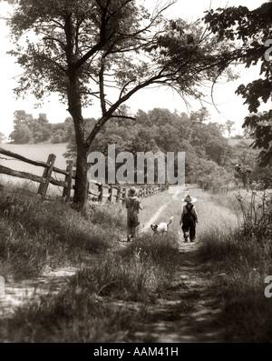 1930 Vue arrière de l'homme et femme dans les chapeaux de paille & BRETELLES WALKING DOWN FARM ROAD AVEC CHIEN ENTRE Banque D'Images