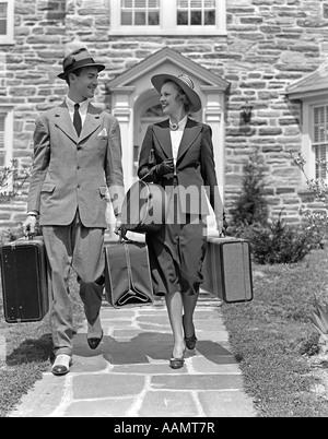 Années 1930 Années 1940 SMILING COUPLE QUITTER ACCUEIL TRANSPORT DES BAGAGES Banque D'Images