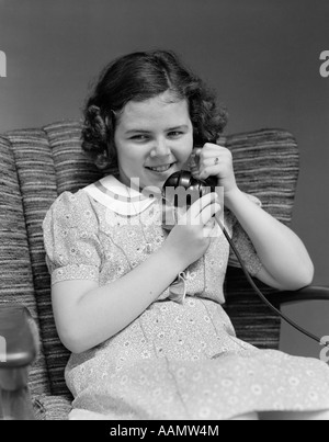 1930 LITTLE GIRL SITTING IN CHAIR TALKING ON TELEPHONE Banque D'Images